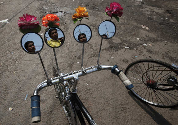 A rickshaw puller is reflected on the installed mirrors of his rickshaw as he waits for passengers on a street in Patna.