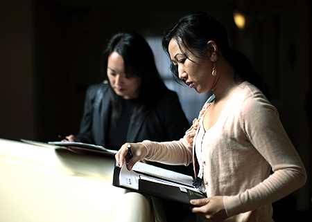 Job seekers Tiffany Tram, 30, (R) and Linda Kim, 30, wait for interviews at a job fair in a hotel in Los Angeles, California.