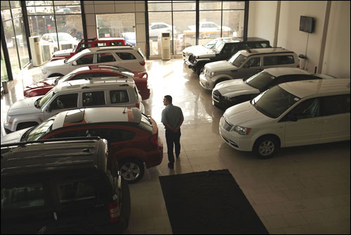 A man walks through a car showroom.