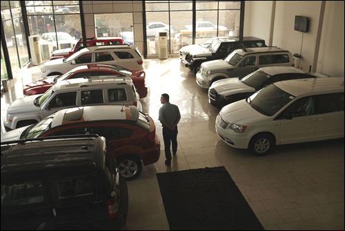A man walks through a car showroom.