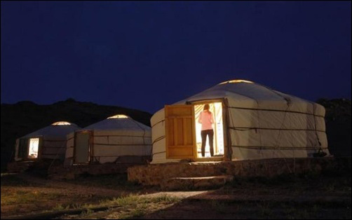 Men wrestle as a girl reacts at a tourist camp near the ruins of Ongi monastery in Mongolia's Dundgovi province.