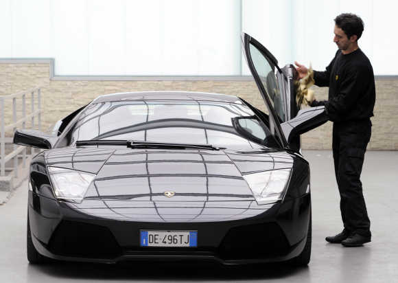 A technician cleans a door of a Lamborghini Murcielago.