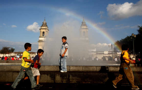 Children play near a fountain at the Parque Central in Guatemala City.