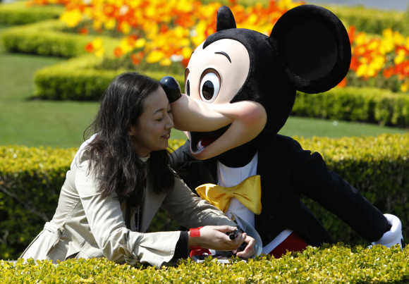 A visitor is kissed by Disney character Mickey Mouse at Tokyo Disneyland in Urayasu, east of Tokyo.