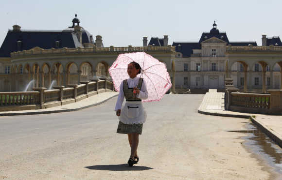A waitress carrying an umbrella walks down the driveway to Chateau Laffitte Hotel located on the outskirts of Beijing.