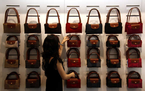 A worker at a store for French luxury goods maker Longchamp adjusts a display of bags in central Beijing.