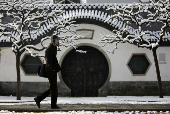A man walks past a Beijing traditional gate covered in snow at Ritan Park in central Beijing.