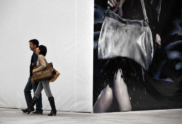 A couple walks past a poster advertising a luxury fashion brand after shopping on a main street in Shanghai.