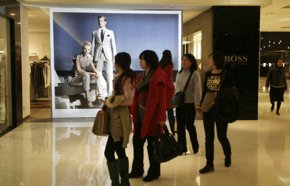Women walk past a Hugo Boss store at a shopping mall in Beijing.