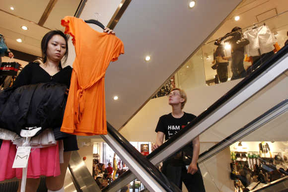 A customer travels down an escalator in the H&M shop in Shanghai.