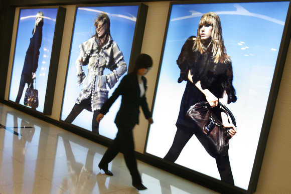 Woman walks past advertisements for designer clothes inside a shopping mall in Beijing.