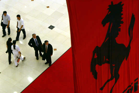 Visitors pass under a huge Ferrari banner at an upscale shopping mall in Shanghai.