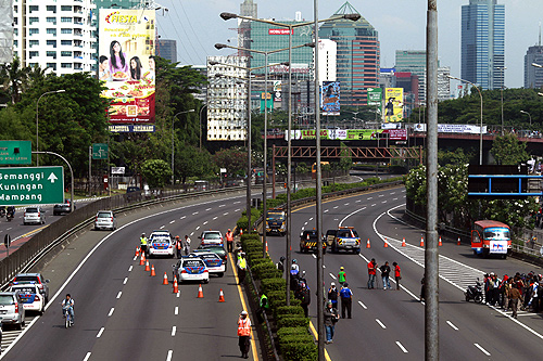 Policemen guard a toll road in Jakarta as students and workers protest against increasing fuel prices in Jakarta.