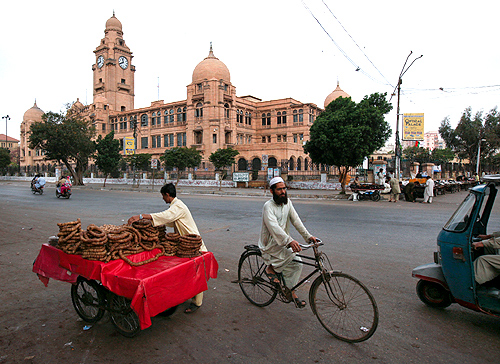 A man sells dry figs from his cart as another rides past on a bicycle in front of the Karachi Municipal Corporation (KMC) building.