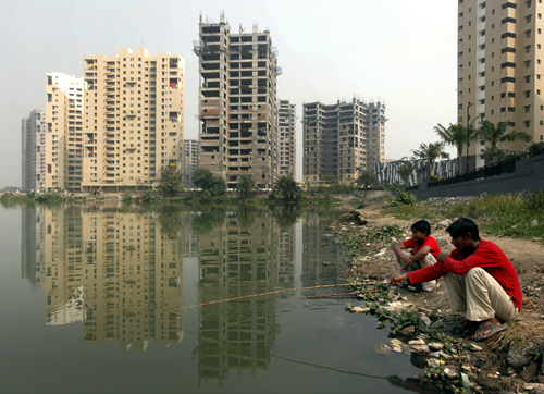 Labourers fish in a pond near a residential estate under construction in Kolkata.