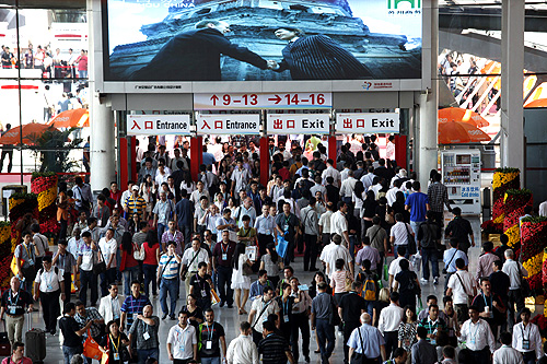Visitors walk through an entrance to China Import and Export Fair, also known as the Canton Fair, in the southern Chinese city of Guangzhou.