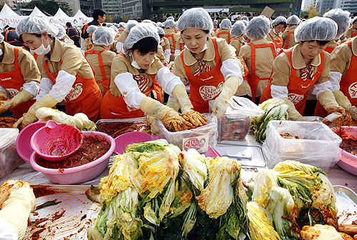 Women make traditional Korean side dish kimchi, or fermented cabbage, at a charity event at the Seoul City Hall Plaza.