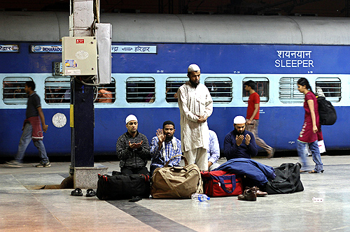 Passengers offer prayers before boarding a train at a railway station in New Delhi.