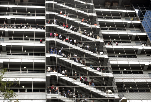 People stand at the emergency stairs in an office building during an earthquake drill in Mexico City.