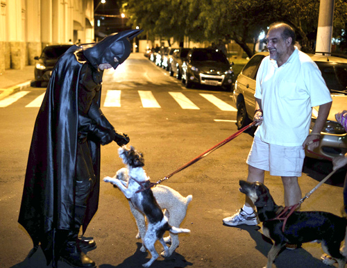 Retired Brazilian police officer Andre Luiz Pinheiro, 50, dressed as super-hero Batman, is greeted by a dog in Taubate city, Sao Paulo.