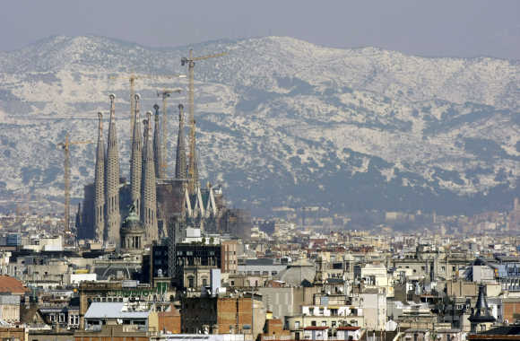 Gaudi's Sagrada Familia and Barcelona's skyline are seen against the backdrop of a snow-covered mount after a snowstorm, Spain.