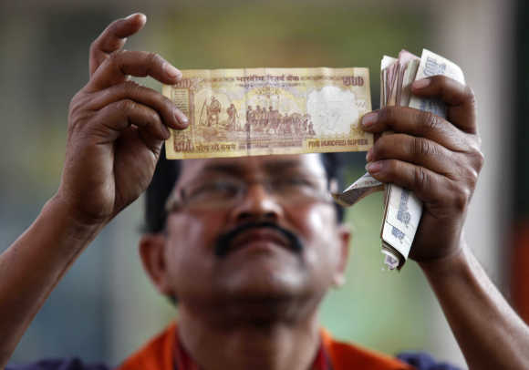 A banker checks a 500-rupee note.