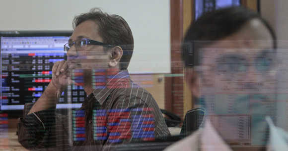 A broker watches a TV news channel as another monitors share prices at a brokerage firm in Mumbai.
