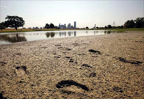 Footprints mark the bank of a partially dried-up pond near downtown Dallas, Texas.