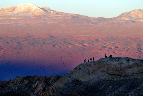 Tourists rest above a hill in Valle de la Luna (Moon Valley) located inside the nature reserve of Los Flamencos in the Atacama Desert, near San Pedro de Atacama in northern Chile.