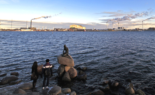 Tourists look at the sculpture of the Little Mermaid, inspired from a fairy tale written by Hans Christian Andersen, a famous landmark of Copenhagen.