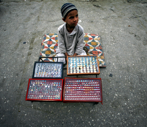 A boy waits for customers while sitting at his father's stall which sells metal rings at a roadside in Quetta.
