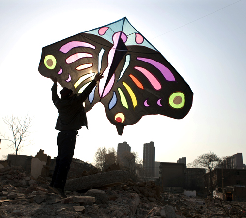 A man holds up a kite as he helps to fly it at a demolition site near residential areas in Shijiazhuang, Hebei province.