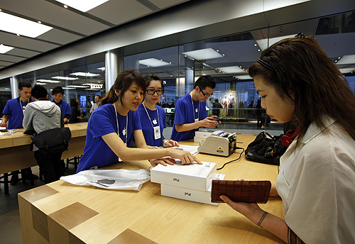A woman (R) collects her new pre-ordered iPad outside an Apple store in Hong Kong.