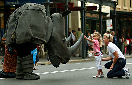 A street performer in a rhinoceros costume jokes with a little girl and her mother in Sydney prior to the start of a rugby match between France and New Zealand.