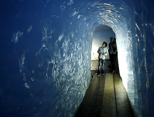 Visitors look at the walls of an ice cave at Rhone glacier in the Swiss Alps at the Furkapass.