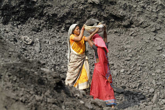 Labourers carry coal at a stockyard of an underground mine in the Mahanadi fields at Dera, near Talcher town, Orissa.