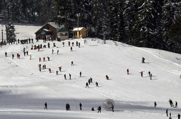 Tourists and skiers ski on a slope in Gulmarg.