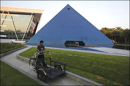 A man pushing a tricycle cart walks in front of a pyramid-shaped building made out of glass in the Infosys campus at Electronics City in Bangalore.