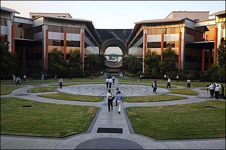 Employees walk in front of a building dubbed the ''washing machine'', a well-known landmark built by Infosys at the Electronics City, Bangalore.