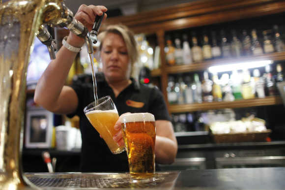 Barmaid pours a glass of beer in Sydney.