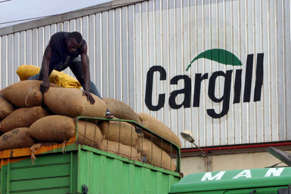 A man gathers bags of cocoa beans at the Cargill factory in Ivory Coast.
