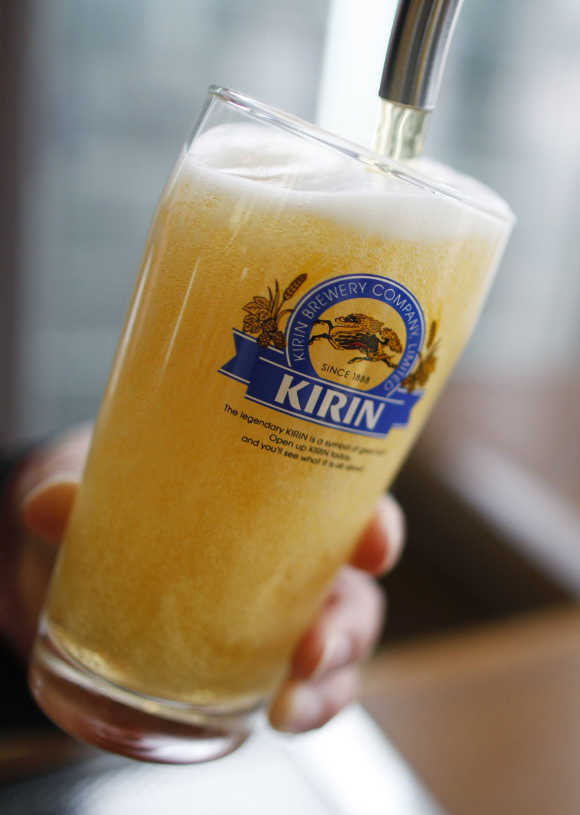 An employee of Kirin Brewery Co fills a glass with Kirin Beer at a tasting room of the company's factory in Sendai, Japan.