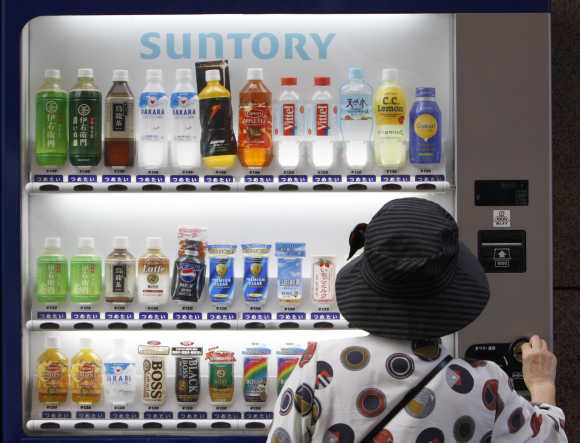A woman purchases Suntory beverage from a vending machine in Tokyo.