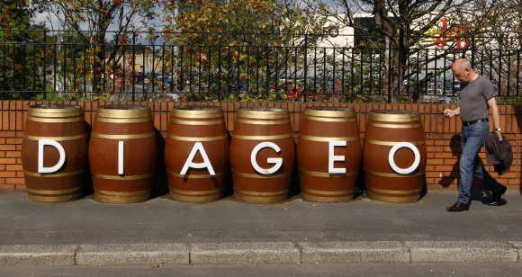 A man walks past barrels outside the Diageo Shieldhall facility near Glasgow, Scotland.