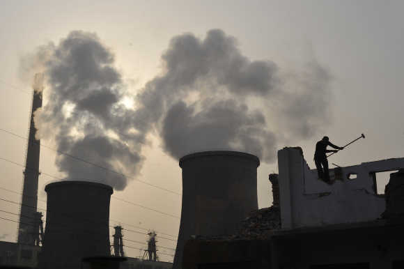 A labourer works near cooling towers of a power plant.