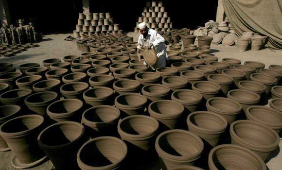 A man holds a clay plate to put under wet pots, used for plants, at his make-shift factory in Peshawar.