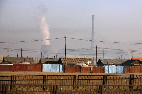 Woman walks past make-shift homes located near chimney stacks from power station on outskirts of Ulan Bator, Mangolia.