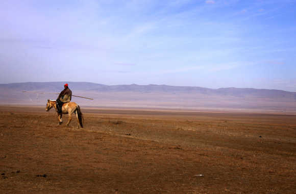 A herder rides a horse as he tends his animals on grasslands located around 200km south-west of the Mongolian capital city Ulan Bator.