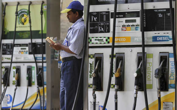 An employee counts money at a fuel station in Kolkata.