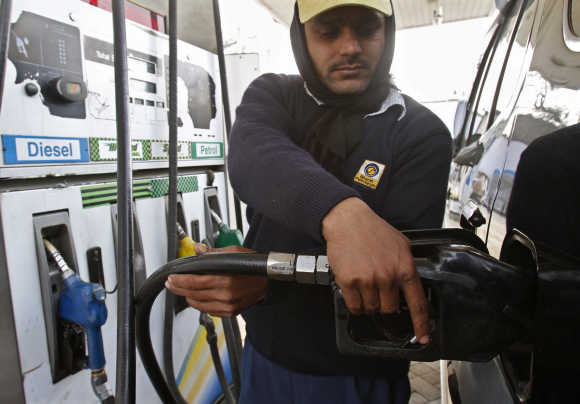 An employee fills a vehicle with diesel at a fuel station in New Delhi.